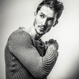 Black-white studio portrait of young handsome man in knitted sweater. Close-up photo. Stock Photos