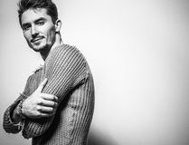 Black-white studio portrait of young handsome man in knitted sweater. Close-up photo. Royalty Free Stock Photos