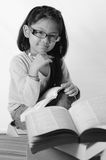 Black & white studying. Little girl sitting with stack of books Stock Photos