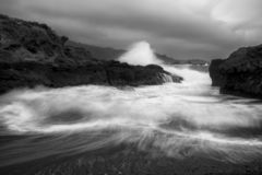 Black and White Surge and Spray as Surf Rolls onto California Coast. Surf and spray in motion onto beach with rocky shoreline in dramatic black and white image stock photos