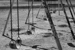 Black and White Swing Set. Black and white photo of an old swing set in a park Stock Photography