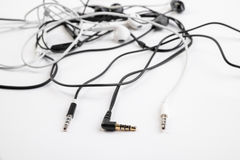 Black and white tangled little headphones lie on a white isolated background. Horizontal frame stock photography