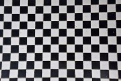 Black and white tile in a checker board pattern. Black and white tile floor in a checker board pattern royalty free stock photography