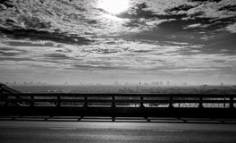 Black and white toned view from the bridge of city near the river and sky and white clouds. Sad, hopeless and death background. City air pollution and global Royalty Free Stock Images