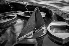 Black and white toys. Close up of boat toys floating on a water tank royalty free stock photography