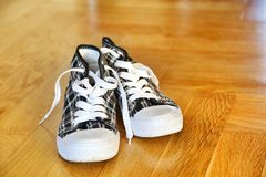 Trainers. Black and white trainers on a wooden floor Stock Photography