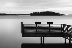 Black and white tranquil scenery of a lake with pier and two chairs