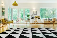Spacious living room with view. Black and white triangle carpet in spacious living room with modern furniture and view on garden Royalty Free Stock Images