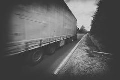 Black and white truck speeding on country highway Stock Image