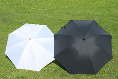 Black and white umbrellas. Lying on the grass stock images