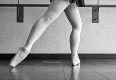 Black and white version of a Ballet Dancer at Barre- tendu derrière en fondu. Ballet dancer at the barre in her pointe shoes doing syllabus work Royalty Free Stock Images