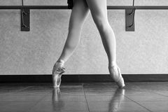 Black and white version of Ballet Dancer En Pointe in 4th. Ballerina at the barre warming up her feet and pointe shoes Stock Images