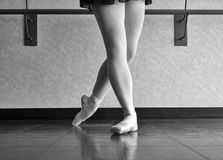 Black and white version of Classical Position of a Ballet dancer. Graceful ballet dancer in classical position preparation in her pointe shoes and practice skirt Stock Photography