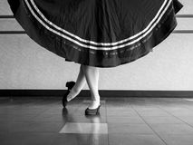 Black and white version of Dancer in Classical position with skirt held in character ballet attire. During dance class in the studio Stock Photography