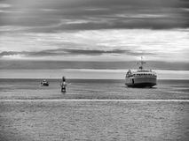 Black and white version of Passenger and Car Ferry In the Ocean Bay. Car and Passenger Ferry boat on the Water leaving from victoria to washington with mountains Royalty Free Stock Photo