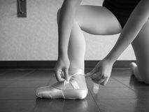 Black and white version of Recreational young female ballet dancer ballerina, in the studio putting on her pointe shoes, tying up