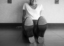 Black and white version of Smiling tap dancer sitting on the dance studio floor in her tap shoes royalty free stock photos