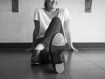 Black and white version of Smiling teenage tap dancer sitting cross legged in dance class relaxing. And enjoying dance class royalty free stock photography