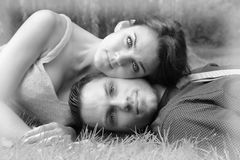 Black and White version of a young couple laying on the grass wi. Th the woman's head resting on the men in a garden setting royalty free stock photo