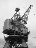 Old crane. Black and white vertical view of old crane at disused docks Stock Image