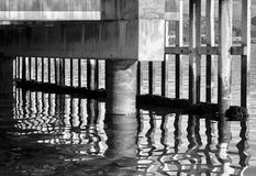 Black and white vibrant Norway quay with water reflections. Black and white vibrant Norway quay reflection abstract background backdrop royalty free stock photo