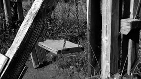 Black and white video of empty broken swing, concept of abandoned child stock footage