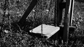 Black and white video of empty broken swing, concept of abandoned child stock video