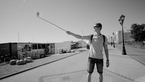 Black and white video of a Traveller holding selfie stick and walking. Happy traveller holding selfie stick. Black and white view of a man walking at the sea stock video footage