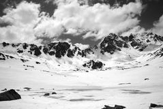 Black and white view on frozen mountain lake covered with snow Royalty Free Stock Photo