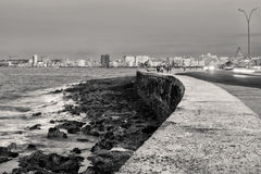 Black and white view of the Malecon seawall in Havana. Black and white view of the famous Malecon seawall in Havana at sunset with a view of the city skyline Stock Photo