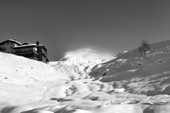 Black and white view on off-piste slope and hotel in winter moun Stock Photos