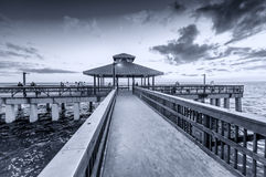 Black and white view of pier at dusk.  Royalty Free Stock Photo