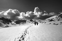 Black and white view on snow plateau with hikers. Stock Images