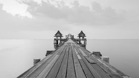 Black and white view of wooden bridge with unfinished temple building Stock Photo