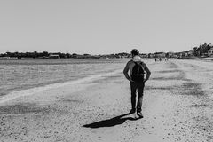 Black & white view of a young man walking on Weymouth beach, Dorset, England. Black & white view of a young man walking on Weymouth beach, Dorset, England Royalty Free Stock Photos