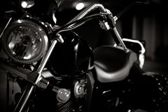 Black and white vintage photo of chopper bike details, chromed, with soft light and reflections, with side leather bags. stock images