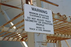 Black and white Warning - Minimum Structure Clearance Applies sign. At a workplace Royalty Free Stock Photography
