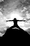 Black and White Warriors Pose Silhouette. Black and White silhouette of a young attractive girl doing the Warriors pose from yoga on top of a rock with the sky Royalty Free Stock Images