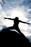 Black and White Warriors Pose Silhouette. Black and White silhouette of a young attractive girl doing the Warriors pose from yoga on top of a rock with the sky Royalty Free Stock Photography