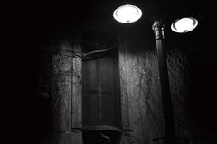 Black and white window at night. Black and white of a street lamp lighting a window at the night stock photography