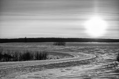 Black and white winter landscape. Curving winter road at sunset in black and white Royalty Free Stock Image