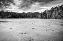 Black and white winter landscape of dangerous cracked ice on frozen Lake Powhatan in North Carolina. Dangerous cracks and holes litter the frozen surface of Lake Stock Photos