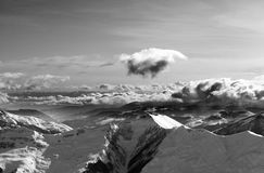 Black and white winter mountains at evening and sunlight clouds Royalty Free Stock Image