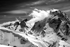 Black and white winter mountains with snow cornice and cloudy sk. Y in nice sun day. Caucasus Mountains, region Dombay. Mount Dombai-Ulgen. View from the top of Stock Photo