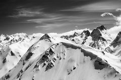 Black and white winter mountains with snow cornice and sky with. Clouds in cold sun day. Caucasus Mountains, region Dombay. View from top of Mount Musa Achitara Royalty Free Stock Images