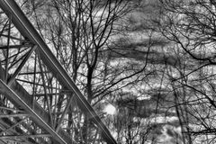 A black and white winter photo of a metallic structure supporting various pipes on concrete blocks running through a forest Stock Photo