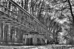 A black and white winter photo of a metallic structure supporting various pipes on concrete blocks running through a forest Royalty Free Stock Images
