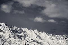 Black and white winter snowy mountains and sky with clouds Royalty Free Stock Images