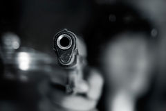 Black and white, woman pointing a old gun to front with one Hand. On dark background stock images