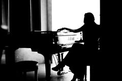 Black and white woman silhouette sitting near piano. Black and white woman silhouette sitting near grand piano Royalty Free Stock Photography